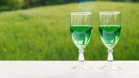 Δύο γυαλιά με την πράσινη λεμονάδα σε ένα υπόβαθρο ενός πράσινου χορτοτάπητα μια άνοιξη καλλιεργούν Άνοιξη και έννοια ημέρας του  απόθεμα βίντεο