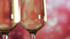 Δύο γυαλιά με τη λαμπιρίζοντας σαμπάνια πέρα από το ροζ με το υπόβαθρο καρδιών o απόθεμα βίντεο