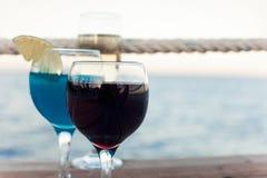 Δύο γυαλιά με το κόκκινο κρασί και τον μπλε χυμό κοκτέιλ Στοκ Εικόνες