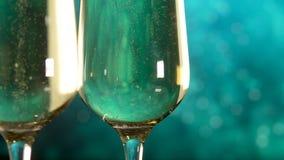 Δύο γυαλιά με το λαμπιρίζοντας κρασί πέρα από το μπλε υπόβαθρο o απόθεμα βίντεο