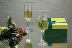 Δύο γυαλιά με το champange, κλάδος δέντρων έλατου με τη διακόσμηση, κιβώτια δώρων σε ένα μαύρο υπόβαθρο με τα πολύχρωμα lightes g Στοκ Φωτογραφία