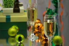 Δύο γυαλιά σαμπάνιας και μπουκάλι καλαθιών Χριστουγέννων, δώρα με την κόκκινη κορδέλλα σατέν, κάλαμοι καραμελών μήλων, κώνοι πεύκ στοκ εικόνες