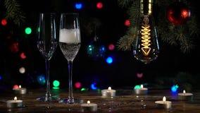 Δύο γυαλιά χύνουν τη σαμπάνια στον πίνακα είναι αναμμένες λάμπες φωτός μια εορταστική ατμόσφαιρα κίνηση αργή απόθεμα βίντεο