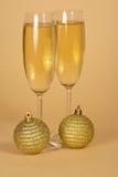 Δύο γυαλιά κρασιού με τη σαμπάνια και δύο χρυσά Στοκ φωτογραφία με δικαίωμα ελεύθερης χρήσης