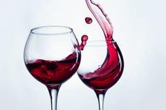 Δύο γυαλιά κρασιού στη χειρονομία ψησίματος με το μεγάλο ράντισμα Στοκ Εικόνες