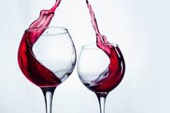 Δύο γυαλιά κρασιού στη χειρονομία ψησίματος με το μεγάλο ράντισμα Στοκ Φωτογραφία