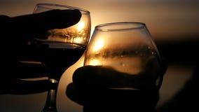 Δύο γυαλιά κρασιού στο υπόβαθρο ενός όμορφου χρυσού ηλιοβασιλέματος με τα εύγευστα ποτά κίνηση αργή 1920x1080 Πλήρες HD απόθεμα βίντεο