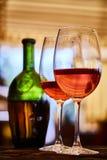 Δύο γυαλιά που γεμίζουν με το κόκκινο κρασί και το μπουκάλι στο υπόβαθρο Στοκ εικόνες με δικαίωμα ελεύθερης χρήσης