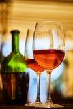 Δύο γυαλιά που γεμίζουν με το κόκκινο κρασί και το μπουκάλι στο υπόβαθρο Στοκ Εικόνες