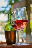 Δύο γυαλιά που γεμίζουν με το κόκκινο κρασί και το μπουκάλι στο υπόβαθρο Στοκ εικόνα με δικαίωμα ελεύθερης χρήσης