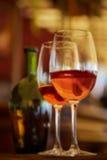 Δύο γυαλιά που γεμίζουν με το κόκκινο κρασί και το μπουκάλι στο υπόβαθρο Στοκ Εικόνα