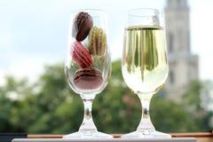 Δύο γυαλιά των γαλλικών macarons και του άσπρου κρασιού Στοκ Φωτογραφίες