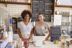 Δύο γυναίκες έτοιμες να εξυπηρετήσουν πίσω από το μετρητή σε μια καφετερία Στοκ εικόνα με δικαίωμα ελεύθερης χρήσης