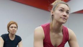 Δύο γυναίκες έχουν μια κατάρτιση στα στάσιμα ποδήλατα στη γυμναστική modrn απόθεμα βίντεο