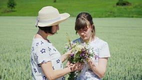 Δύο γυναίκες εξετάζουν μια ανθοδέσμη των wildflowers απόθεμα βίντεο