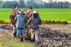 Δύο γυναίκες καθοδηγούν ένα άροτρο που τραβιέται από τα άλογα σχεδίων Στοκ φωτογραφία με δικαίωμα ελεύθερης χρήσης