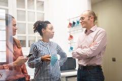 Δύο γυναίκες και ένας άνδρας σε μια κουζίνα γραφείων Στοκ εικόνες με δικαίωμα ελεύθερης χρήσης