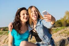Δύο γυναίκες, κολλούν έξω τη γλώσσα τους και selfie υπαίθρια στοκ εικόνα με δικαίωμα ελεύθερης χρήσης