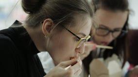 Δύο γυναίκες με τα ποτήρια τρώνε chopsticks τα κινεζικά τρόφιμα και συζήτηση της εργασίας στην αρχή απόθεμα βίντεο