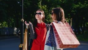 Δύο γυναίκες μιλούν ενθουσιωδώς για τις αγορές τους Στα χέρια που κρατούν τις τσάντες αγορών απόθεμα βίντεο