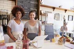 Δύο γυναίκες πίσω από το μετρητή σε μια καφετερία, ευρεία γωνία Στοκ Εικόνες