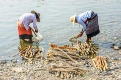 Δύο γυναίκες πλένουν το ξύλο thanakha στον ποταμό Mann στοκ φωτογραφία