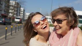 Δύο γυναίκες, πορτρέτο στενές, μητέρα και κόρη σε μια οδό πόλεων Η ηλιόλουστη ημέρα, γυναίκες με τα γυαλιά γελά και αγκαλιάζει απόθεμα βίντεο