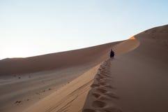 Δύο γυναίκες που αναρριχούνται στο μεγάλο αμμόλοφο μπαμπάδων κατά τη διάρκεια της ανατολής, έρημος Στοκ φωτογραφία με δικαίωμα ελεύθερης χρήσης