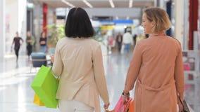 Δύο γυναίκες που γυρίζουν πίσω στη κάμερα στη λεωφόρο Καυκάσιες κυρίες που τελειώνουν τις αγορές τους Ελκυστικό θηλυκό δύο απόθεμα βίντεο