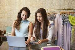 Δύο γυναίκες που εργάζονται σε ένα κατάστημα ενδυμάτων που χρησιμοποιεί έναν φορητό προσωπικό υπολογιστή στοκ φωτογραφία