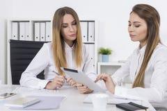 Δύο γυναίκες που εργάζονται σε ένα δωμάτιο γραφείων με μια ταμπλέτα Στοκ φωτογραφία με δικαίωμα ελεύθερης χρήσης