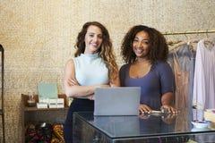 Δύο γυναίκες που εργάζονται στον ιματισμό αποθηκεύουν το κοίταγμα στη κάμερα στοκ φωτογραφία