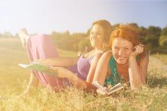 Δύο γυναίκες που διαβάζονται στη χλόη Στοκ φωτογραφία με δικαίωμα ελεύθερης χρήσης