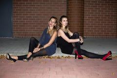 Δύο γυναίκες που κάθονται σε μια συγκράτηση στοκ φωτογραφίες