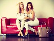 Δύο γυναίκες που κάθονται στον καναπέ που παρουσιάζει την τσάντα Στοκ Φωτογραφίες