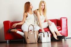 Δύο γυναίκες που κάθονται στον καναπέ που παρουσιάζει τις τσάντες Στοκ φωτογραφίες με δικαίωμα ελεύθερης χρήσης