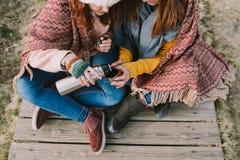 Δύο γυναίκες που κάθονται στο λιβάδι μοιράζονται ένα φλυτζάνι του ζωμ στοκ εικόνα