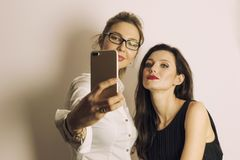 Δύο γυναίκες που κάνουν ένα selfie χρησιμοποιώντας το έξυπνο τηλέφωνο και χαμογελώντας σε ένα ουδέτερο γκρίζο υπόβαθρο στοκ φωτογραφίες