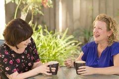 Δύο γυναίκες που μοιράζονται και που κουβεντιάζουν πέρα από τον καφέ Στοκ φωτογραφία με δικαίωμα ελεύθερης χρήσης