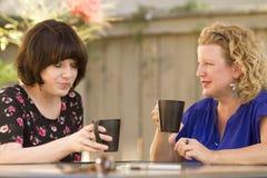 Δύο γυναίκες που μοιράζονται και που κουβεντιάζουν πέρα από τον καφέ Στοκ εικόνα με δικαίωμα ελεύθερης χρήσης