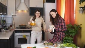 Δύο γυναίκες που πίνουν το χυμό από πορτοκάλι στην κουζίνα και την τροφή μεταξύ τους φρούτα απόθεμα βίντεο