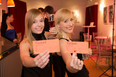 Δύο γυναίκες που παρουσιάζουν τα εισιτήρια θεάτρων ή κινηματογράφων Στοκ φωτογραφία με δικαίωμα ελεύθερης χρήσης