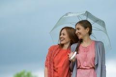Δύο γυναίκες που περπατούν το πάρκο στη βροχή και τη συζήτηση Φιλία και επικοινωνία ανθρώπων στοκ εικόνες