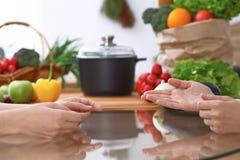 Δύο γυναίκες που συζητούν νέες επιλογές στην κουζίνα, κλείνουν επάνω Ανθρώπινα χέρια δύο ατόμων που στον πίνακα μεταξύ Στοκ Εικόνες