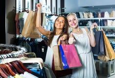 Δύο γυναίκες που φαίνονται συγκινημένες και που φέρνουν πολλές τσάντες εγγράφου στο fashio Στοκ Φωτογραφία