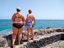 δύο γυναίκες που φορούν το μπικίνι και τα γυαλιά ηλίου σε έναν μαύρο τοίχο πετρών κοντά στη θάλασσα που προσέχει ένα surfer winds στοκ φωτογραφία με δικαίωμα ελεύθερης χρήσης