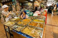 Δύο γυναίκες πωλούν το ασιατικό γρήγορο γεύμα με το κρέας μέσα στην αγορά με τις λιχουδιές και τα προϊόντα καλλιέργειας στοκ εικόνα