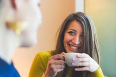 Δύο γυναίκες σε έναν καφέ που χαμογελά και που φαίνεται μεταξύ τους Στοκ εικόνες με δικαίωμα ελεύθερης χρήσης