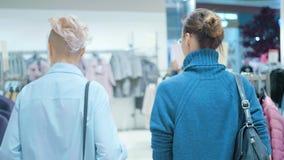 Δύο γυναίκες σε μια μπουτίκ που επιλέγει ένα φόρεμα απόθεμα βίντεο