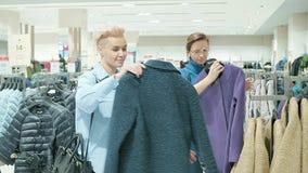 Δύο γυναίκες σε μια μπουτίκ που επιλέγει ένα φόρεμα φιλμ μικρού μήκους